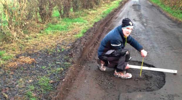 Sinn Fein councillor Terry Hearty measures potholes on a south Armagh road. Pic Armagh i