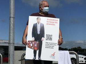 An aviation worker holds a banner challenging Chancellor Rishi Sunak to intervene to protect jobs. (Rebecca Black/PA)