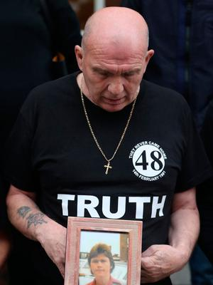 Eugene Kelly, looks at a photo of his 17-year-old brother Robert, who died in the 1981 fire