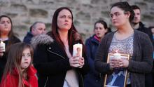 Widow Joanne McGibbon (centre) with her daughters Michaela and Seana at a vigil in the grounds of Holy Cross Church, Ardoyne