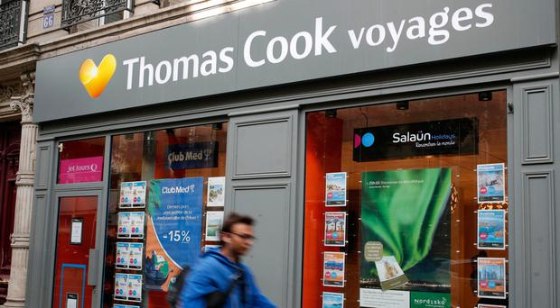 People walk past a Thomas Cook travel shop in Paris yesterday