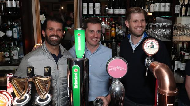 Hugh McNally with Donald Trump Jr. (left), and Eric Trump (right), the sons of US President Donald Trump, pour drinks and meet locals in the village of Doonbeg in Co Clare, on the first day of US President Donald Trump's visit to the Republic of Ireland.