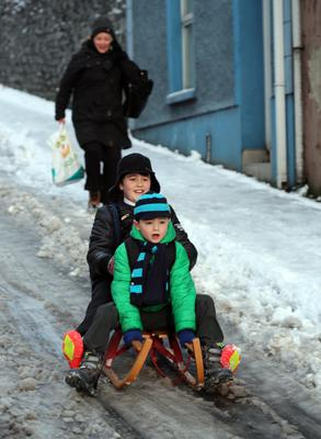 Brothers Brenn (10) and Aodan (7) Doherty sledge along Creggan Hill to the Model Primary School in Derry