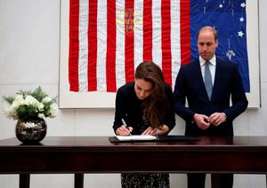 William, Duke of Cambridge looks on as Catherine, Duchess of Cambridge, signs a book of condolence at the US Embassy in London yesterday morning