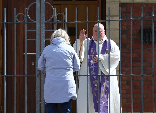 Father Paddy McCafferty hears confession at the gates of Corpus Christi chapel in Ballymurphy