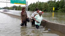 Evacuees wade down a flooded section of Interstate 610 in floodwaters from tropical storm Harvey