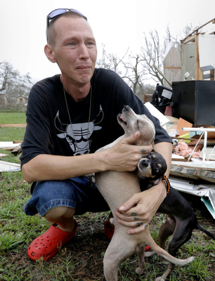 Sam Speights tries to hold back tears while holding his dogs and surveying the damage to his home