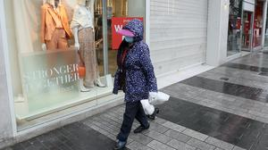 A woman wearing a protective face mask passes a shop window in Belfast (Brian Lawless/PA)