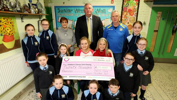 Anna McDonald, from the Children's Cancer Unit Charity, receives a cheque from Cliodhna and Nancy Craig. Also pictured are some of Charlie's classmates at St Joseph's Primary School and principal, Mr Declan Murray (c), with Maura Lowry and Dee French, from St Patrick's Parish Centre