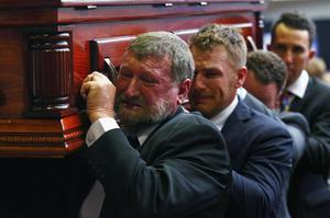 A tearful Gregory Hughes (left), father of cricketer Phillip Hughes, helps to carry his son's coffin during his funeral service in Macksville, Australia, yesterday