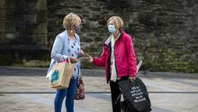 Two woman chat while wearing faces masks in Derry City (PA)