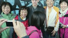 Archbishop of Canterbury Justin Welby meets a group of Chinese tourists as he pays a visit to the peace wall in Cupar Way in west Belfast