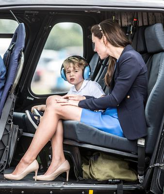 Prince George overawed by the noise at the air tattoo before being shown a Squirrel helicopter by the Duke and Duchess