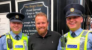 The Open champion with Sgt Gillolley and Insp Cullen outside the Boar's Head on Capel Street in Dublin yesterday