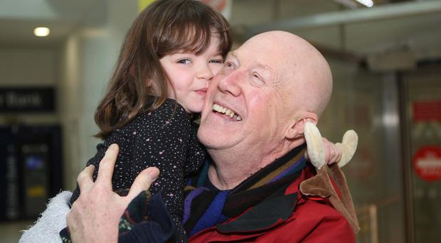 Little Emme hugs her grandfather Paul Smith at Belfast City Airport yesterday
