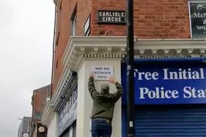 An illegal street sign is put up in Belfast by a Lasair Dhearg member
