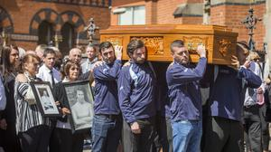 Members of the Wave FC carry the coffin of Billy McConville