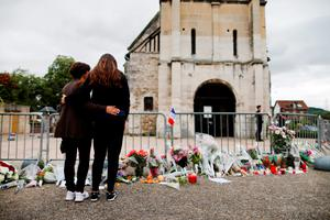 People stand in front of a make shift memorial in front of the Saint-Etienne du Rouvray church on July 27, 2016, after the priest Jacques Hamel was killed on July 26 in his church during a hostage-taking claimed by Islamic State group.