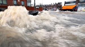 A manhole cover being ripped out of it's hole by the pressure of the water on Skegoneill Avenue 2014