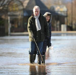 A couple make their way through floodwater in Worcester city centre as the River Severn has reached its highest level in recent years