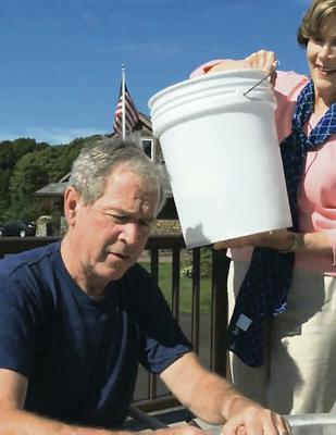 Laura Bush pours a bucket of ice water over her husband George