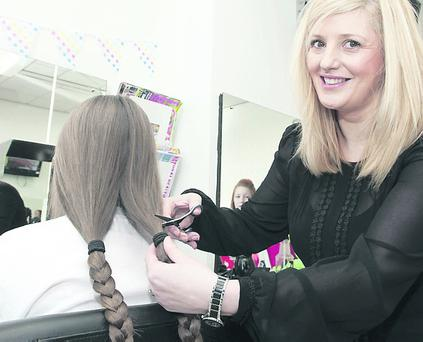 Sandra Holden prepares to make the first cut with eleven years old Ciara Harkin