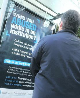 A woman reads about the latest Historical Institutional Abuse Inquiry on a bus stop poster
