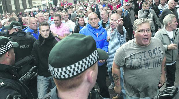 Loyalists and police outside St Patrick's Church in Belfast's Donegall Street last year