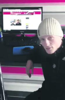 Jamie Bryson in his Facebook video with news coverage of police plans to arrest him playing in the background on a TV screen
