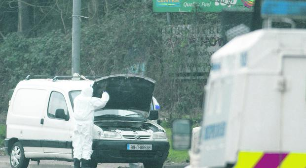 A police forensic officer examines the van which contained the four mortar tubes