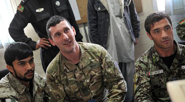 Staff Sergeant Trevor Beck, 34, from Belfast, with members of the Afghan Police (Cpl Mike O'Neill RLC/MoD/Crown Copyright/PA)