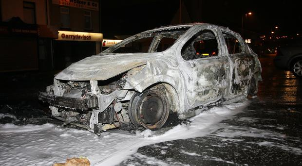 The shell of a torched car after rioting on the Carnmoney Road, Glengormley