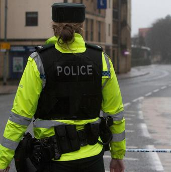 The PSNI is investigating after a suspected gun was found near the scene of a bomb attack near three police officers on a coastal path