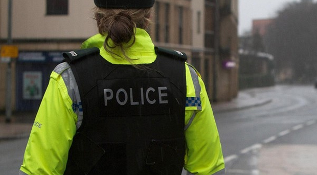 An armed gang smashed into the Belfast home and shot one of the occupants