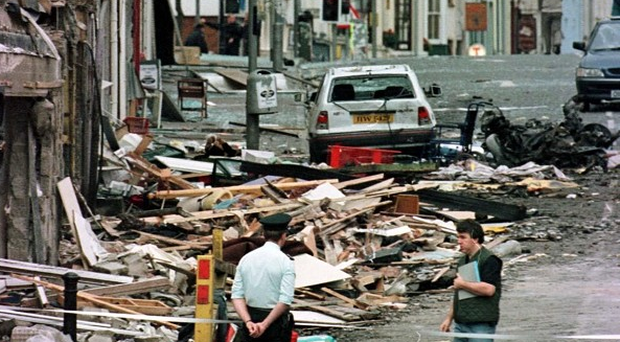 A police officer looks at the damage caused by a bomb explosion in Market Street, Omagh, Co Tyrone in 1998