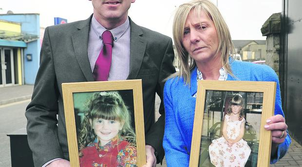Raymond and Maire Ferguson with pictures of their daughter Raychel outside the inquest