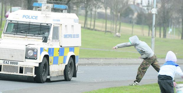 Nationalist youths throw rocks at police officers near the 32 County Sovereignty Easter Rising commemoration rally on Monday in Derry's Creggan estate