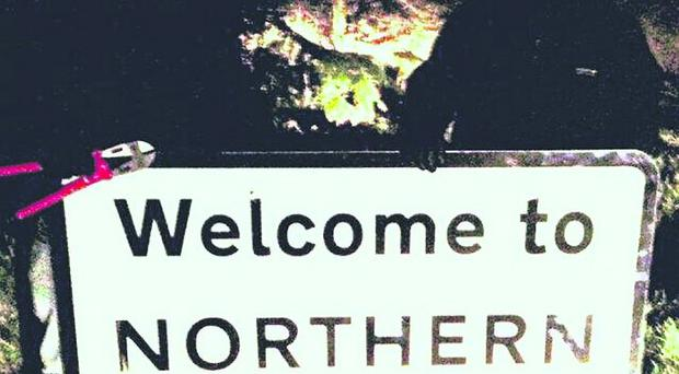 Two men with bolt-cutters obscure their identities as they pose with a Welcome To Northern Ireland sign