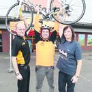 Belfast Telegraph news editor Colin O'Carroll picks up his new bike from Halfords in Newtownabbey ahead of the Maracycle from Belfast to Dublin and back. Colin is pictured with store manager Jonathan Revill and Cooperation Ireland's Janet Brennan.