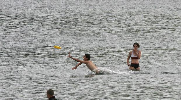 Revellers enjoy a swim at Carnlough Beach in Co Antrim. Northern Ireland beaches are becoming increasingly more littered