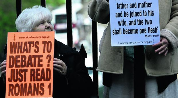 Protestors demonstrate outside the entrance to the Church of Scotland General Assembly