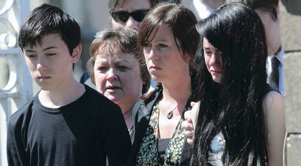 Colin Poland's wife, centre, and his children Jess and Cora at his funeral in Bryansford yesterday.