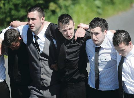 Kevin O'Hare's friends comfort each other during the funeral Mass at Finnis, near Dromara