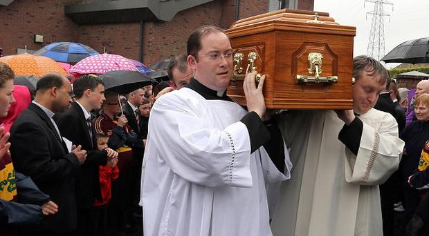 Priests carry the coffin of Father Matt Wallace from Holy Trinity church in west Belfast