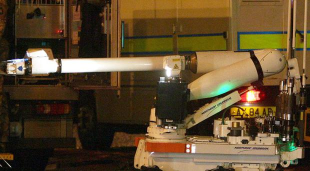 An army bomb disposal expert examines the booby trap bomb found under a policeman's car in Belfast last year