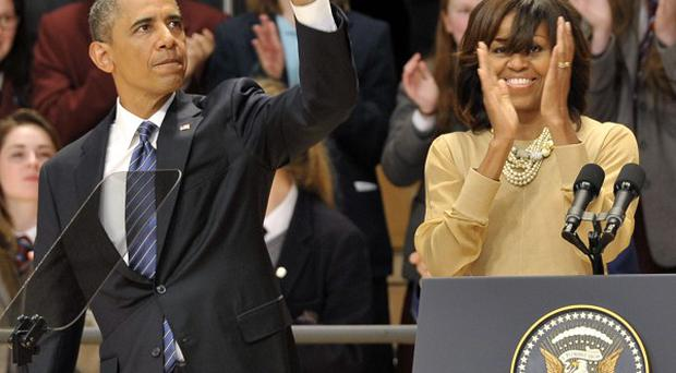 US President Barack Obama and his wife Michelle Obama wave after he delivered a keynote address at Waterfront Hall in Belfast