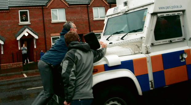 Gerry Kelly on the bonnett of a police landrover