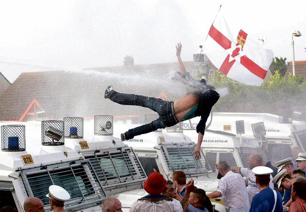 Blowback: Loyalist on police landrover hit by water cannon in Woodvale