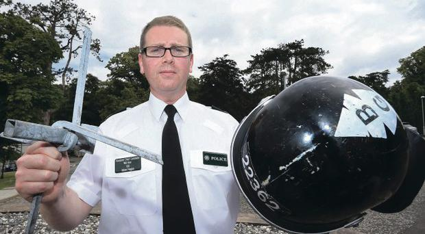Assistant Chief Constable Will Kerr holds a police officer's helmet