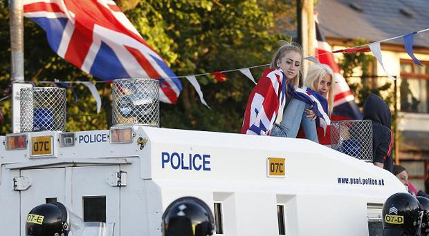 Loyalist protesters sit on top of an armoured police vehicle in North Belfast as trouble flared for the third night (AP)